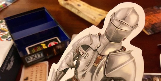 Exit The Game: The Forbidden Castle's knight being held over assorted game components.