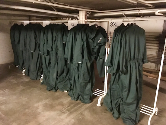 A clothing rack with hunter green jumpsuits.