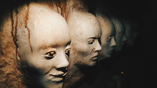 In-game: a weathered wall of creepy plaster faces.