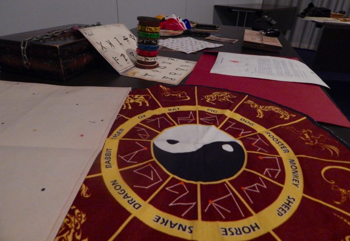 In-game: A table of assorted puzzle components including a Chinese zodiac, a locked box, and other strange puzzle components.