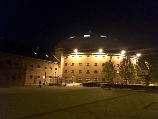 The Breda Prison Dome lit at night.