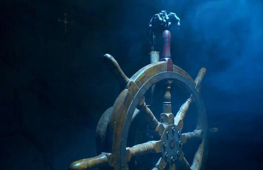 In-game: Wooden ship wheel with a skeletal hand pointing at the top of the wheel.