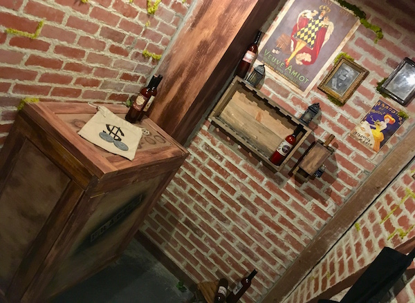 In-game: A brick wine cellar with wooden crates and old photos.