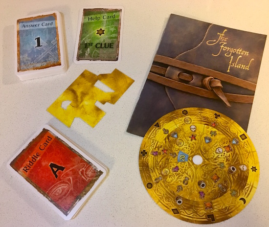 The answer card deck, riddle card deck, a stack of help cards, a strange item, the decoder wheel, and the Forgotten Island journal.