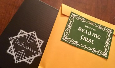 """A green letter that reads """"Part Two Read Me First,"""" atop a sealed manila envelope and the Post Curious box."""