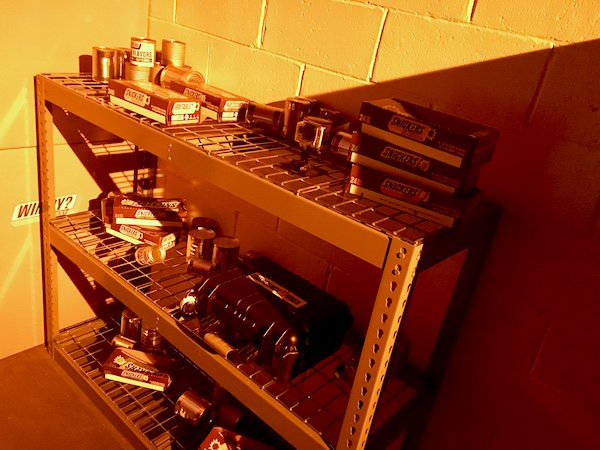 In-game: wire shelving covered in canned food and snickers boxes.