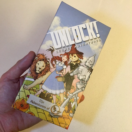Unlock! The Adventures of Oz box art features Dorothy, the Lion, the Tin Man, and the Scarecrow waling the Yellow Brick Road.