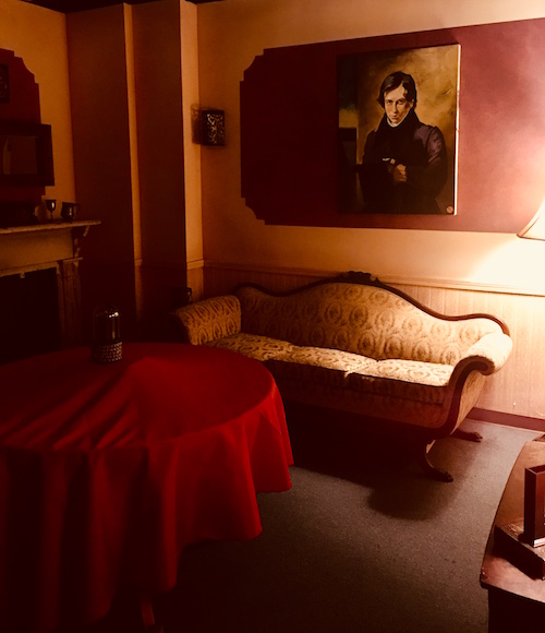 In-game: An old parlor with a red clothed table, couch, and a painted portrait of a vampire.