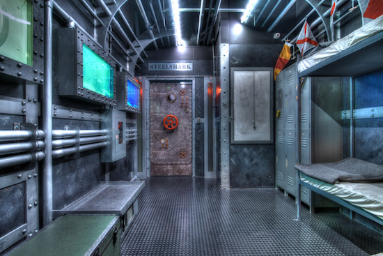 In-game: a shiny filtered image of the interior of the bunk. Metal walls and pipes.