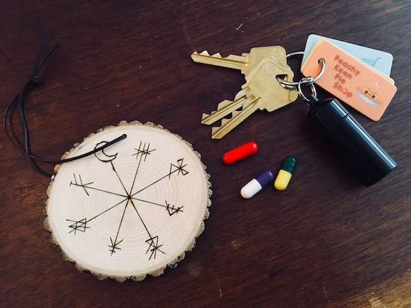 In-game: A keychain, a collection of pills, and an engraved wooden medallion.