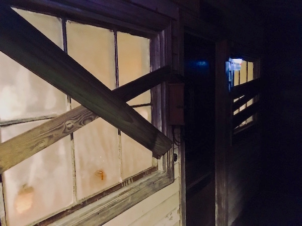 In-game: the exterior for a rundown and boarded up home.