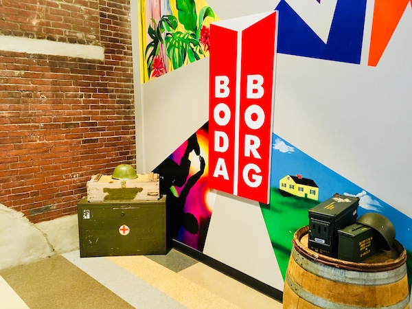 Boda Borg's logo beside some of the militaristic props from their game Platoon.