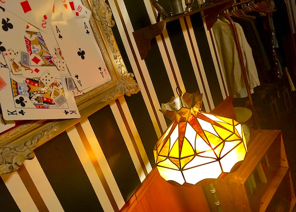 In-game: Close up of a glowing lamp illuminating a picture frame collage of playing cards of varying sizes.