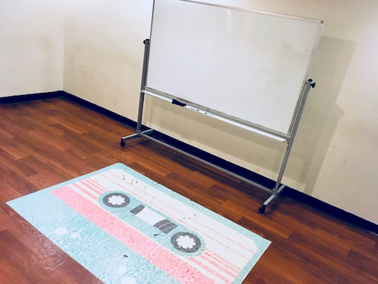 In-game: a plain white walled room with a whiteboard and a large fading cassette tape decal on the floor.