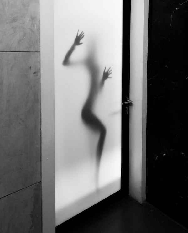 The silhouette of a woman pressed up against a translucent door.