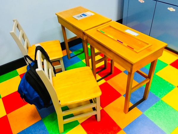 In-game: A pair of classroom desks with strange projects resting on top of them.