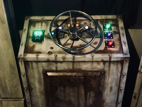 In-game: a captain's wheel and glowing buttons, switches, and indicators.