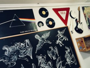 In-game: a 90s bedroom with Pink Floyd album art, a zodiac poster, records, and a guitar.