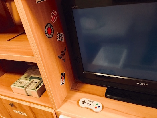 In-game: a TV and game console in a 90s bedroom.