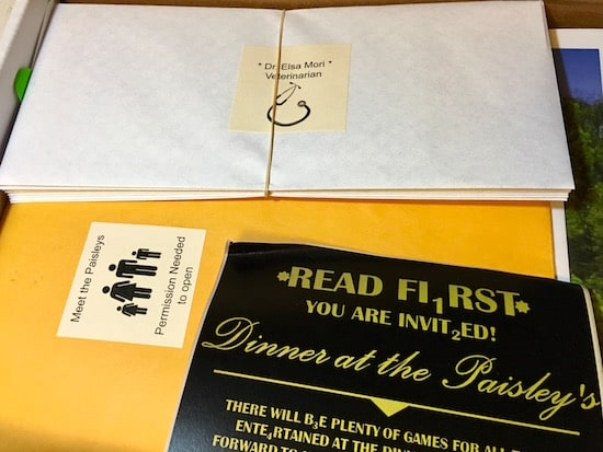 Murder at the Paisley's box opened, revealing a party invitation and character envelopes.