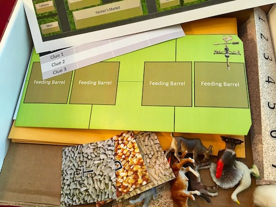 Puzzle components including tiles with animal feed, little plastic farm animals, and farm maps.