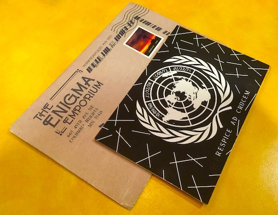 The Enigma Emporium envelope and a UN postcard.