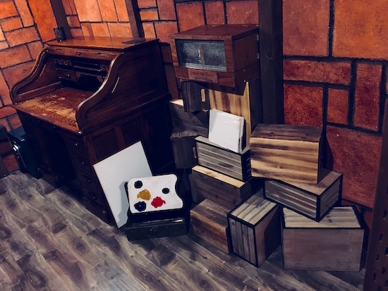 In-game: a rolltop desk beside a stack of crates and an artest palet.