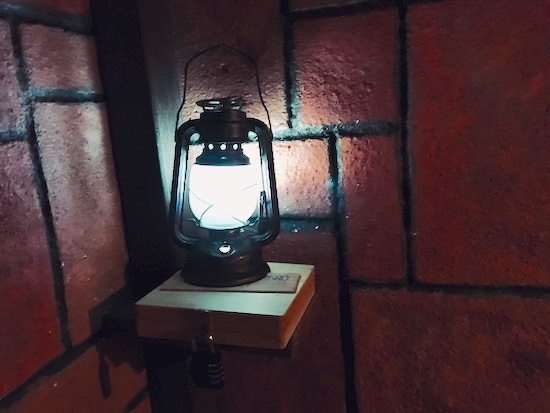 In-game: a glowing lantern resting on a lock box in a stone tunnel.