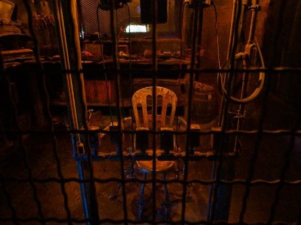 In-game: A torture chair behind a cage.