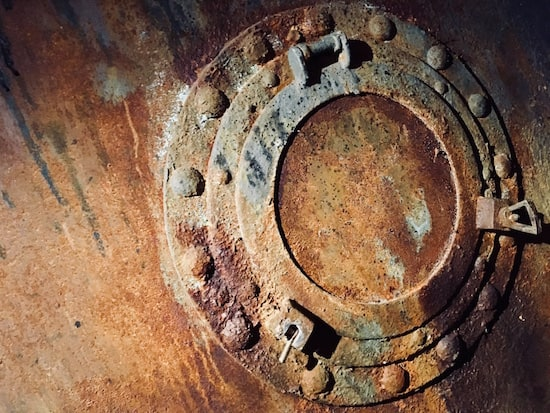 In-game: A closeup of a rusty and weathered porthole.