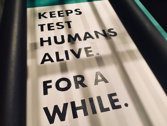 "In-game: A sign that reads, ""Keeps test humans alive. For a while."""