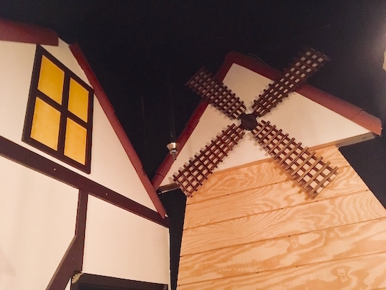 In-game: a view of the exterior of a home adjacent to a windmill.