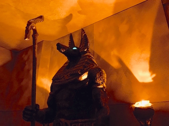 In-game: a large torch-lit stature of Anubis with glowing green eyes.
