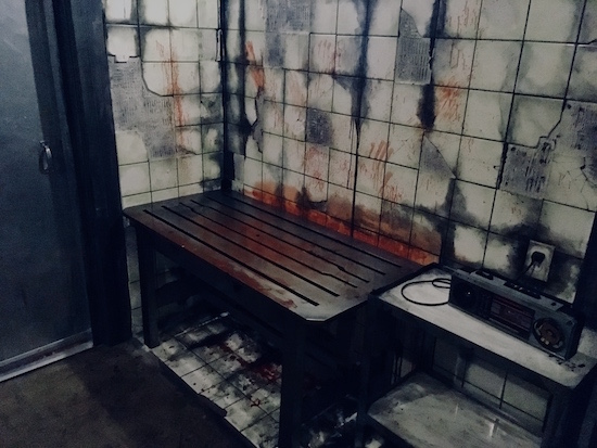 In-game: a bloody and damaged tile wall, a boom box, and a blood soaked table.