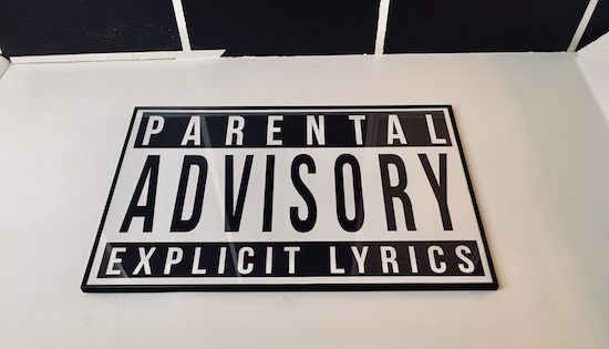In-game: a large Parental Advisory Explicit Lyrics poster hanging on the wall.