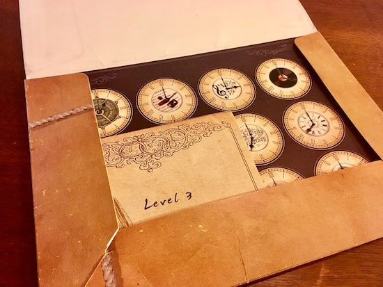 """In-game: A folder with a piece of paper with a matrix of clock faces, and an envelope labeled, """"Level 3."""""""