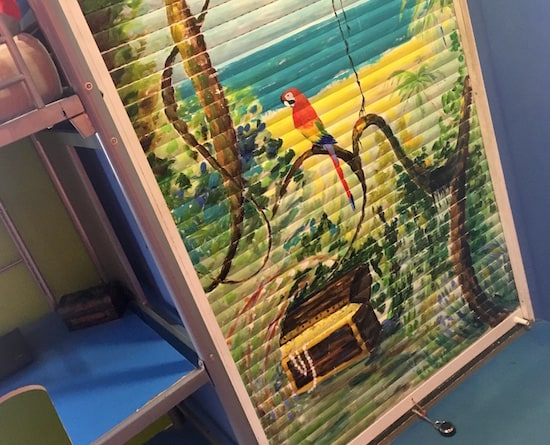 In-game: Nicolai's closet door is painted with a tropical island, a parrot, and pirate treasure.