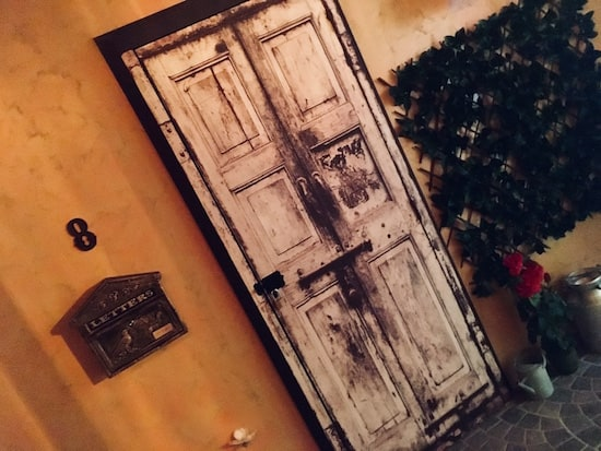 In-game: A weathered, white door addressed number 8 with a large mailbox hanging beside it.