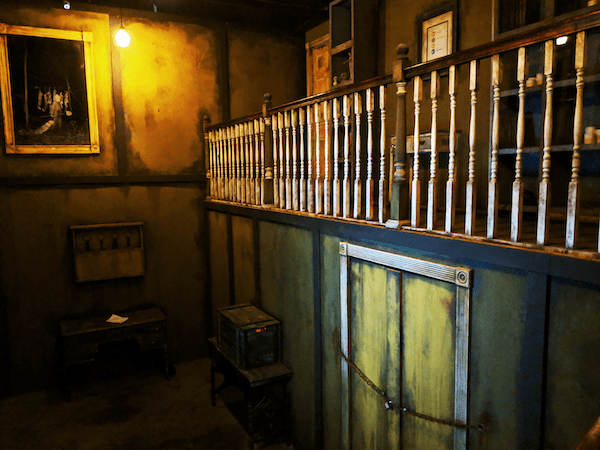 In-game: The two story grand parlor featuring a door chained shut under a a large balcony.