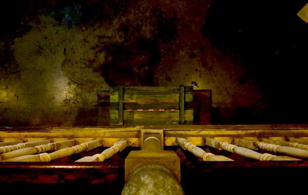 In-game: View over the balcony to a wooden box with a faint red glow emanating from it.