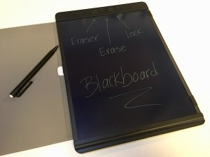 A large boogie board blackboard, pointing out the eraser button, the erase button, and the lock switch.