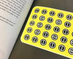 In-book, page shows the first puzzle: a grid of circles that look like flat-head screwheads, some oriented vertically, others, horizontally.