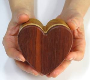 Two hands holding a heart shaped wooden box.