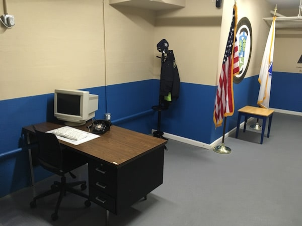 In-game: The police station, featuring an American & Massachusetts flags, a coat hanger with a uniform and a desk with a computer.