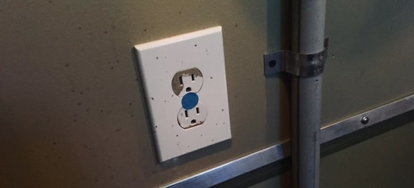 An electrical outlet with a blue do not touch sticker.