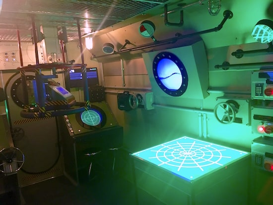 In-game: The bridge of the submarine. A map glows green.
