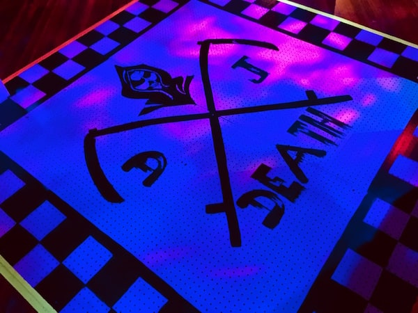 In-game: a dance floor with DJ Death's skull and cross scythe logo.
