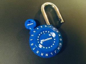 Blue alphanumeric locker-style padlock open with a reset key inserted.
