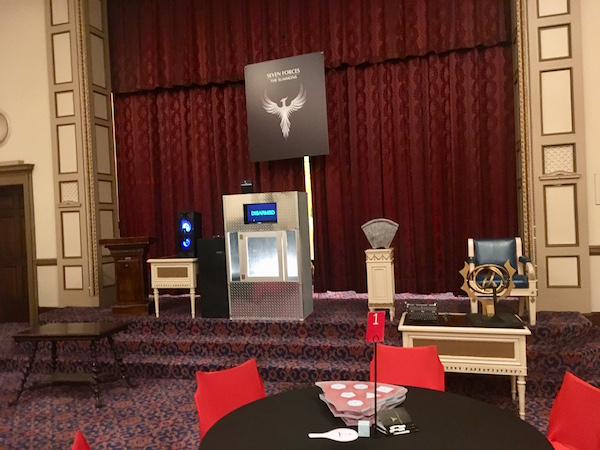 In-game: A stage at the front of teh room features an assortment of strange pieces of technology and mystical artifacts.
