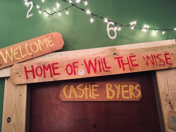 """In-game: Christmas lights strung with the numbers 2 & 6 hanging from them. Below it, a door with wood panels that have the words, """"Home of Will The Wise"""" and """"Castle Byers,"""" painted on them."""